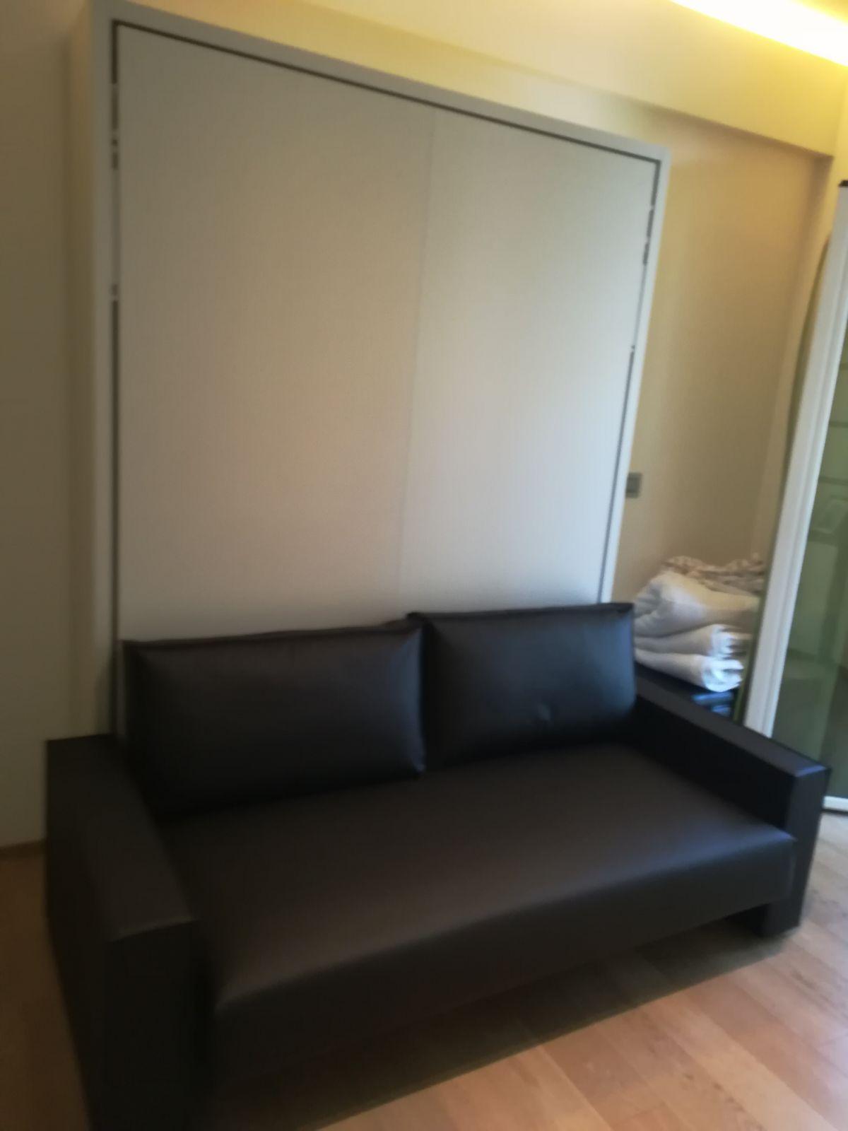 Arredamento monolocale a Riccione con letto a scomparsa con divano